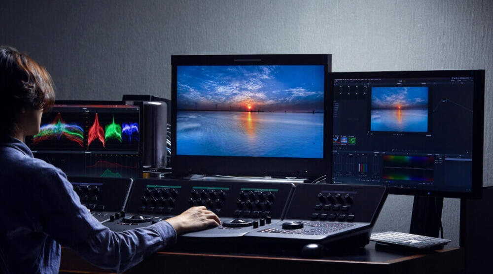 Color correction and grading specialist working on movie project using high quality equipment
